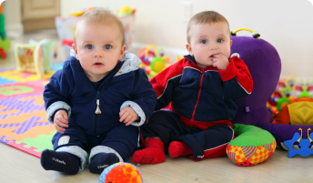 Cute baby brothers playing in the nursery