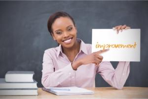 a teacher showing improvement word written on a paper